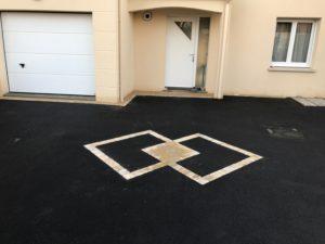 terrassement cours de maison en goudron noir et pavés